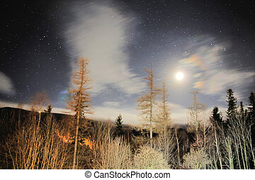 Amazing night sky in the mountains with the stars, clouds and the moon