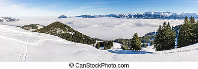 Amazing panoramic View from Snow Mountain to snowy Mountain Range above foggy cloud layer. Sea of clouds. Rangiswangerhorn, Allgau, Bavaria, Germany.