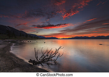 Amazing red sunset over a mountain lake.