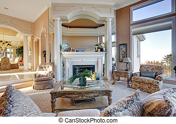 Large rich living room with fireplace accomplished with rustic and antique furniture, colomns and great designed ceiling