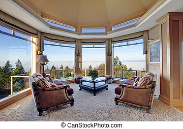 Round corner with soft carpet floor, cathedral ceiling and glass wall with antique chairs