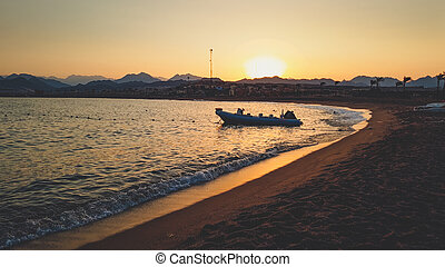 Amazing silhouette photo of inflatable boat with motor rocking on calm ocean waves at the sandy shore against sunset sky