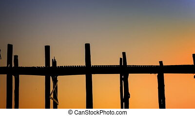 Amazing silhouettes of monks on the ancient wooden bridge. Burma, Mandalay