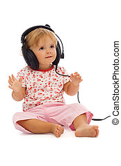 Little toddler girl listening to music on large headphones - isolated on white - with a bit of shadow