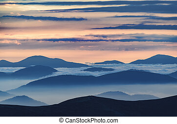 Amazing sunrise high in the mountains with blue and pink mountain silhouettes