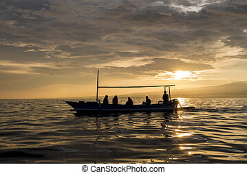 Amazing sunrise with silhouette of people in small boat in...