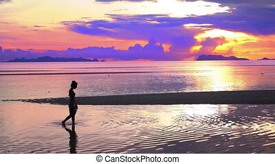 Amazing Sunset and Silhouette of a Girl Walking Alone.