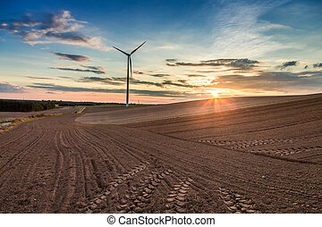 Amazing sunset at brown field and wind turbine, Poland