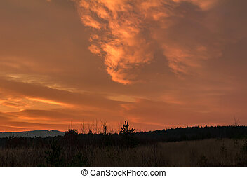 Amazing sunset clouds with land silhouette