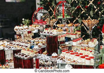 Amazing sweet buffet with dishes put on red vases
