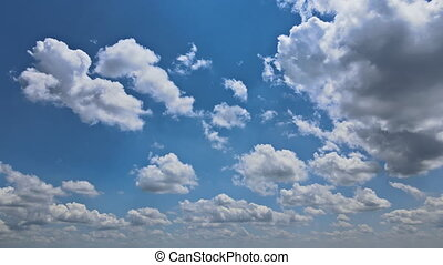 Amazing time lapse of soft white clouds moving through beautiful thick fluffy clouds slowly on the clear blue sky in pure daylight.