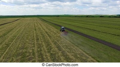 Amazing top view of a tractor working a grass field in Po Valley