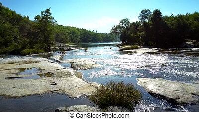 mountain river rapids run among rocks under sunlight