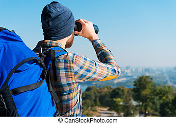 Amazing view. Handsome young bearded man carrying backpack and looking through binoculars at view