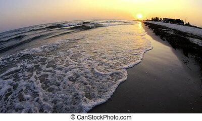 Amazing view of sea waves on the beach at sunset.