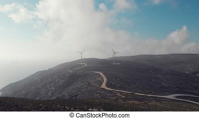 amazing windmill silhouettes operate on green hilltop under...