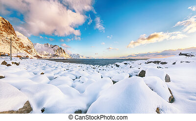 Amazing winter view near Hamnoy village with round rocks and snowy mountain peaks on background