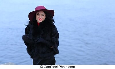 Amazing woman in a red hat on the background of water...