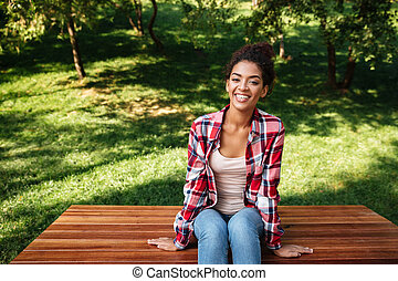 Amazing young african woman sitting outdoors in park