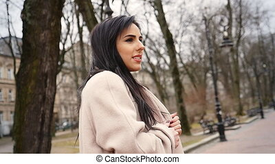 Amazing young lady wearing fashionable grey coat relaxing in the street.
