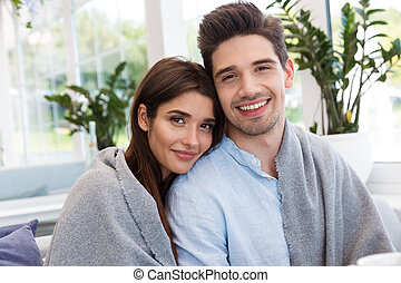 Amazing young loving couple sitting in cafe hugging with each other.