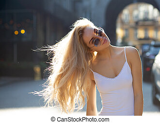 Amazing young model with long hair wearing glasses, posing at the passage in rays of sun. Copy space