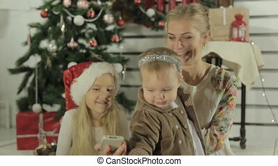Amazing young mother doing selfie on the phone with her little blond girls