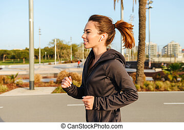 Amazing young sports woman running outdoors