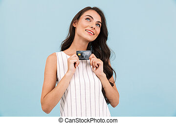 Amazing young woman posing isolated over blue background wall holding credit card.