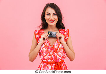 Amazing young woman posing isolated over pink background wall holding credit card.