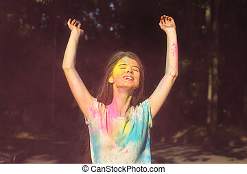 Amazing young woman posing with Holi powder exploding around her
