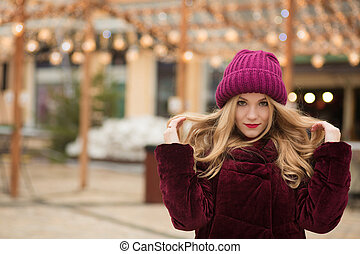 Amazing young woman with long hair posing on the background of garland at the street in Kiev