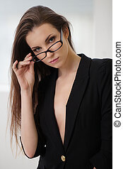 Ambitious and beautiful. Beautiful young woman in black suit looking at camera and adjusting her glasses