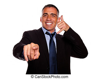 Portrait of a ambitious smiling broker pointing on black suit against white background