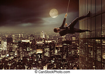 Ambitious businessman climbing on the skyscraper