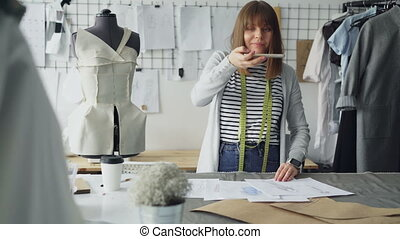 Ambitious creative female tailor is placing garment sketches...