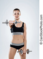 Ambitious girl exercising with dumbbells on a grey background