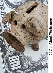 Ambitious Piggy Bank - A Piggy Bank Rests on a $100 Bill.