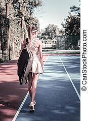 Ambitious successful woman heading to tennis training