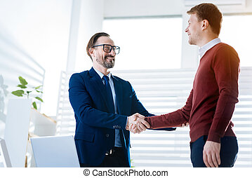Ambitious two colleagues shaking hands