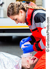 Ambulance doctor giving oxygen to female victim