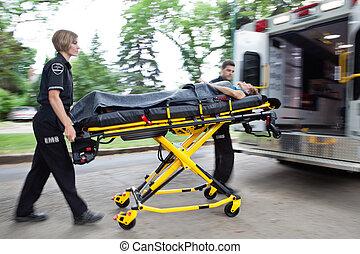 Ambulance Rush - Man and woman ambulance team rushing a...