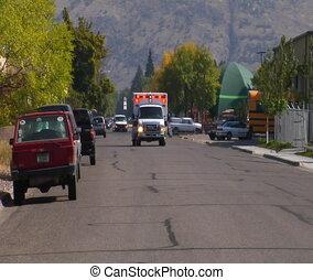 Ambulance with lights speeding down street