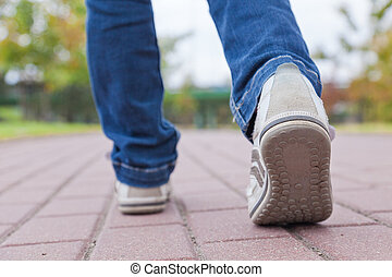ambulante, pavimento, zapatos del deporte