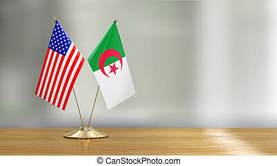 American and Algerian flag pair on a desk over defocused background