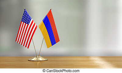 American and Armenian flag pair on a desk over defocused background