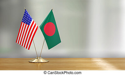 American and Bangladesh flag pair on a desk over defocused background