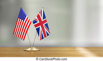 American and British flag pair on a desk over defocused background