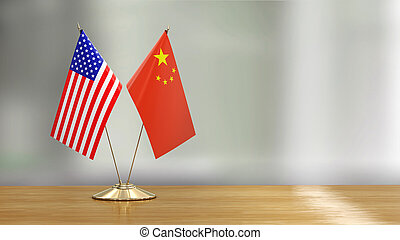 American and Chinese flag pair on a desk over defocused background