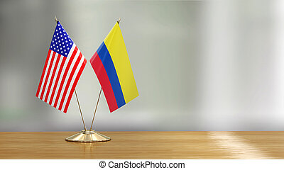 American and Colombian flag pair on a desk over defocused background